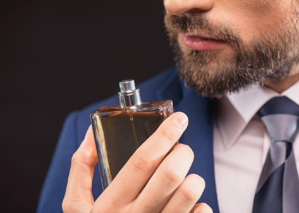 barbat cu parfum in mana